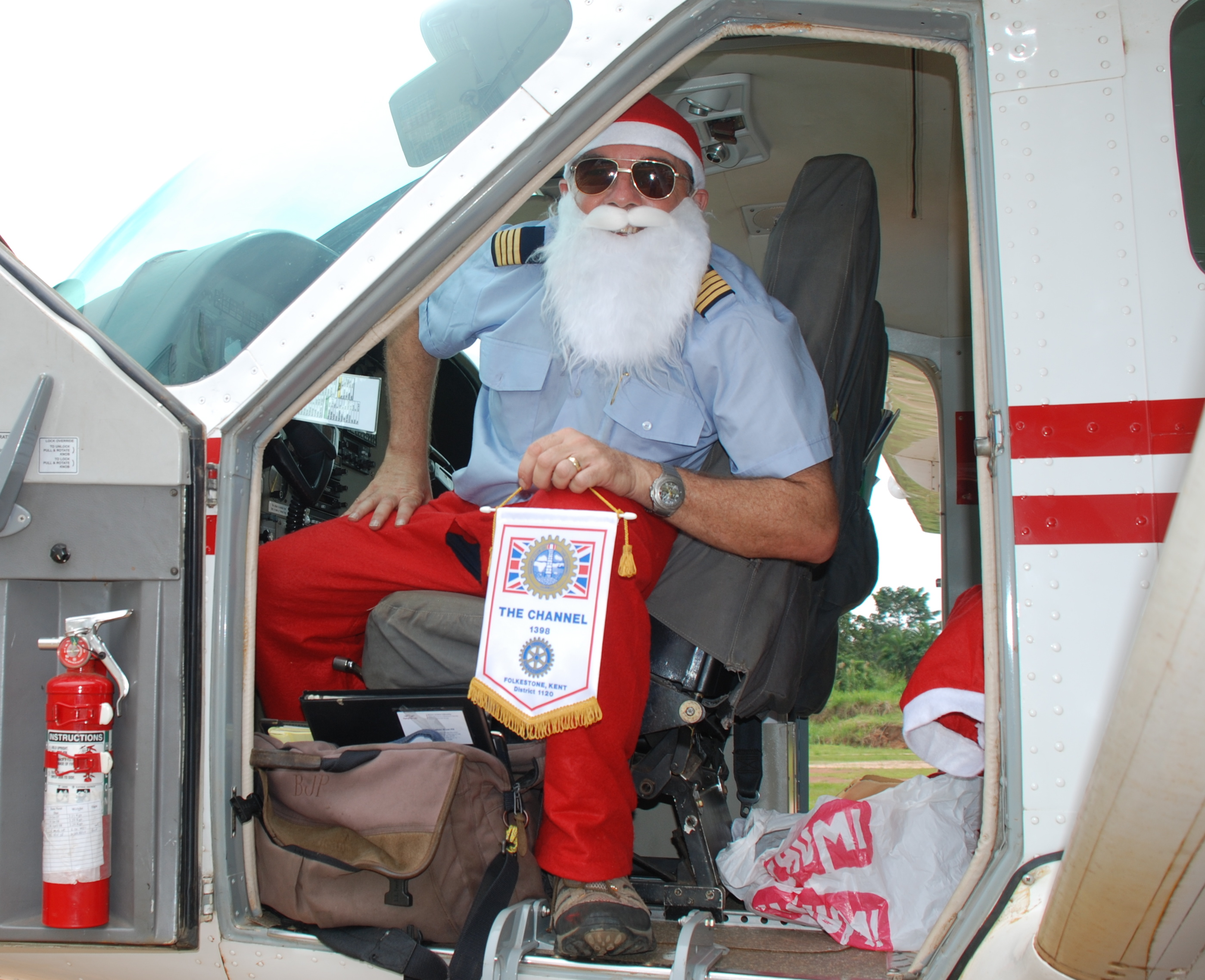 Rotary Santa Run 2008 MAF pilot Brian Pill with our banner on a Uganda landing strip