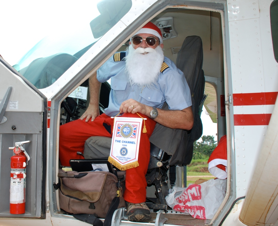 Rotary Santa Run 2008 MAF pilot Brian Pill with our banner on a Uganda landing strip